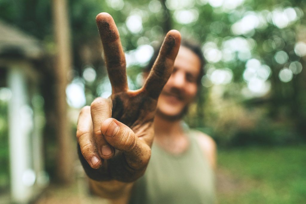 man with dirty hands doing the peace sign - Photo by Eddie Kopp on Unsplash